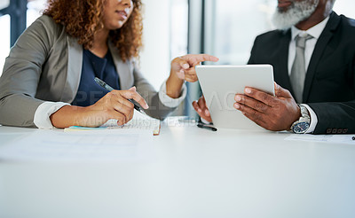 Buy stock photo Closeup shot of two businesspeople working together on a digital tablet in an office