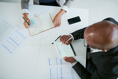 Buy stock photo High angle shot of two businesspeople having a meeting in an office