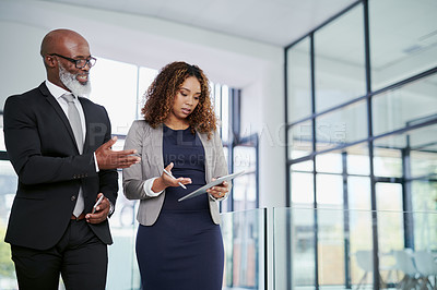 Buy stock photo Shot of two businesspeople using a digital tablet while walking in an office