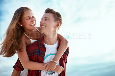 Buy stock photo Shot of a happy young enjoying a piggyback ride outdoors