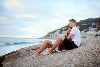 Buy stock photo Shot of a happy young couple relaxing on a rock together at the beach
