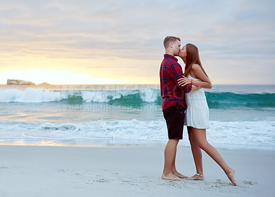 Buy stock photo Shot of a happy young couple kissing at sunset on the beach