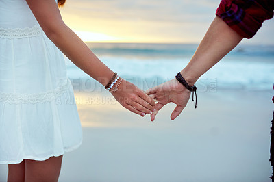 Buy stock photo Cropped shot of a young couple holding hands at the beach