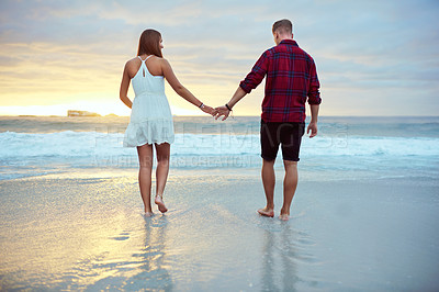 Buy stock photo Shot of a young couple going for a romantic walk along the beach