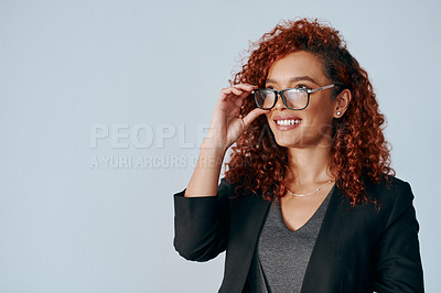Buy stock photo Shot of a young businesswoman looking thoughtful against a grey background