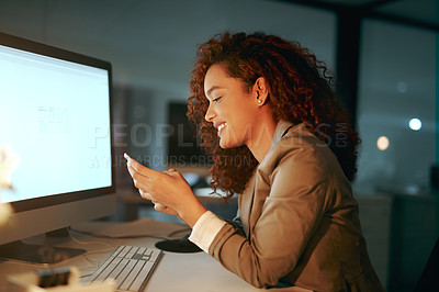 Buy stock photo Shot of a young businesswoman using a cellphone while working late in an office