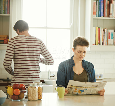 Buy stock photo Shot of a young woman reading a newspaper while her husband prepares breakfast at home