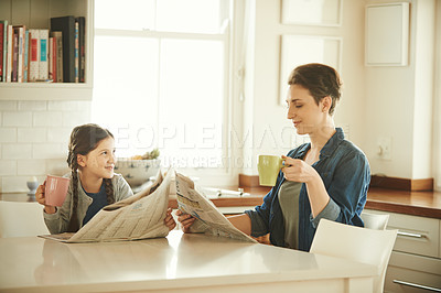 Buy stock photo Shot of a mother and her little daughter reading a newspaper in the morning at home