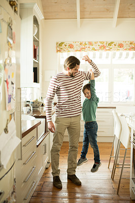 Buy stock photo Shot of a little boy holding on to his father's arm as he lifts him up at home