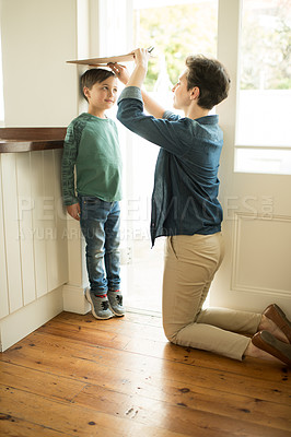 Buy stock photo Shot of a mother measuring her little son's height at home