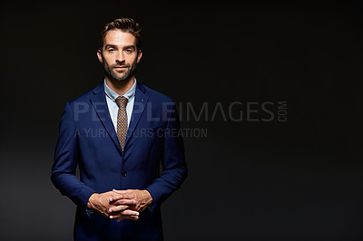 Buy stock photo Studio portrait of a handsome young businessman posing against a dark background