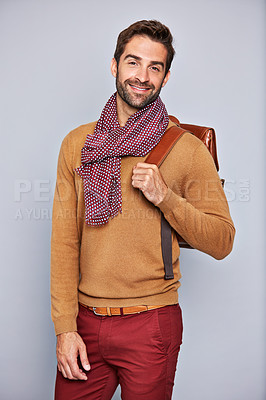 Buy stock photo Studio portrait of a handsome young man carrying a backpack against a grey background