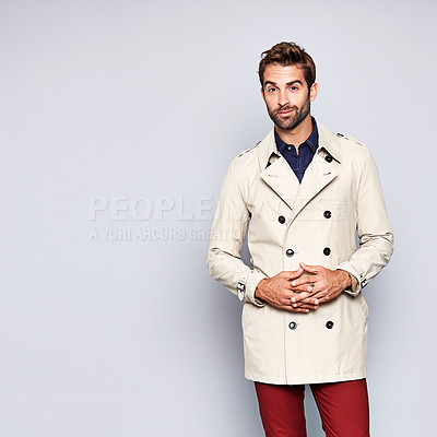 Buy stock photo Studio portrait of a handsome young man posing in a trench coat against a grey background