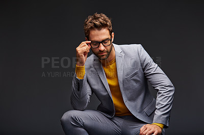 Buy stock photo Studio shot of a handsome young businessman sitting against a grey background