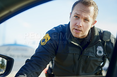 Buy stock photo Cropped shot of a handsome young male traffic officer working at a roadblock
