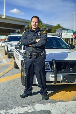 Buy stock photo Full length portrait of a handsome young policeman standing with his arms crossed while out on patrol