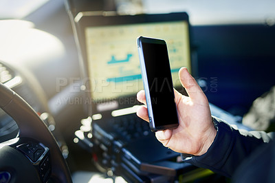 Buy stock photo Cropped shot of an unrecognizable male police officer using his cellphone while out on patrol
