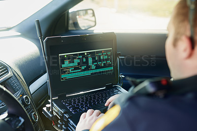 Buy stock photo Cropped shot of an unrecognizable male police officer using his laptop while out on patrol