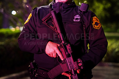 Buy stock photo Cropped shot of an unrecognizable policeman standing with his assault rifle while out on patrol