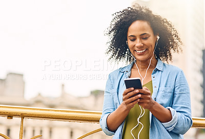 Buy stock photo Shot of a young woman listening to music on her cellphone while out in the city