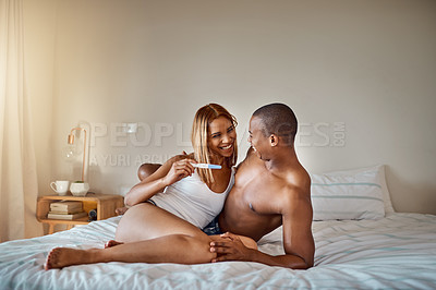 Buy stock photo Shot of a young couple looking happy after taking a home pregnancy test