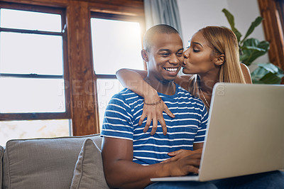 Buy stock photo Shot of a happy young man using a laptop on the sofa while his wife kisses him from behind