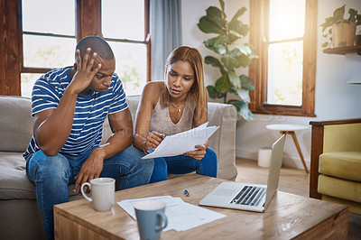 Buy stock photo Shot of a young couple using a laptop and looking stressed while going through their paperwork at home