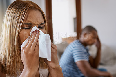 Buy stock photo Shot of a young woman blowing her nose with her husband in the background at home