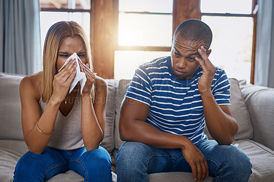 Buy stock photo Shot of a young woman blowing her nose with her husband sitting next to her on the sofa