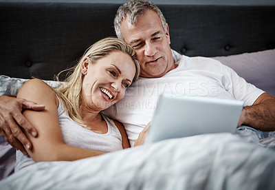 Buy stock photo Shot of a mature couple using a digital tablet while lying in bed