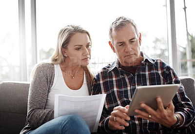 Buy stock photo Shot of a mature couple using a digital tablet while going through their paperwork together on the sofa at home