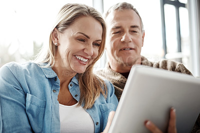 Buy stock photo Shot of a mature couple using a digital tablet while relaxing together on the sofa at home