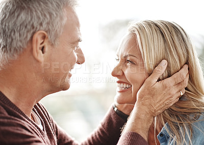 Buy stock photo Shot of an affectionate mature couple sharing a romantic moment at home