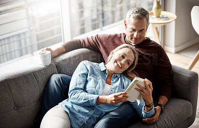 Buy stock photo Shot of a mature couple reading a book together while relaxing on the sofa at home