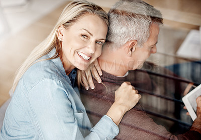 Buy stock photo Shot of a mature woman hugging her husband while he uses a digital tablet on the sofa at home