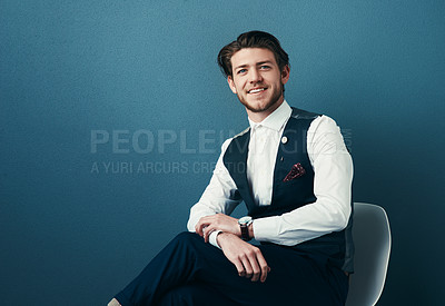 Buy stock photo Studio shot of a handsome young businessman posing against a blue background