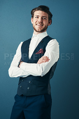 Buy stock photo Studio shot of a handsome young businessman standing with his arms crossed against a blue background
