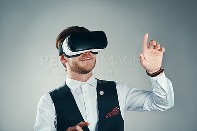 Buy stock photo Studio shot of a handsome young businessman using a vr headset against a grey background