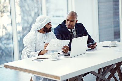 Buy stock photo Shot of two businessmen using a digital tablet and laptop while having a discussion in a modern office