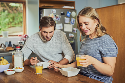 Buy stock photo Cropped shot of a young couple having breakfast at home