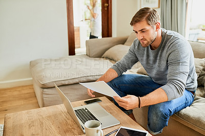 Buy stock photo Shot of a young man planning his home budget in the living room at home