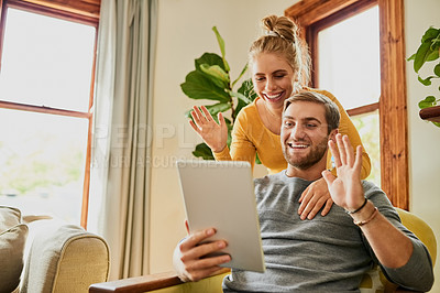 Buy stock photo Cropped shot of a young couple video calling using a tablet in the living room at home