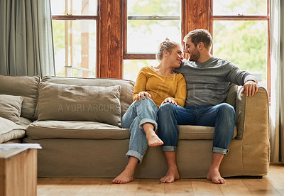 Buy stock photo Shot of a young couple being affectionate on the sofa in the living room at home