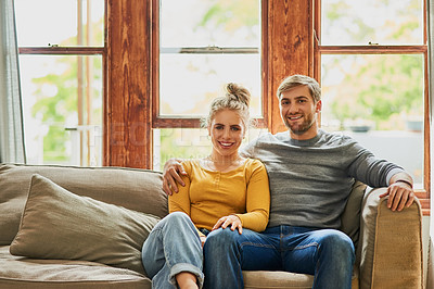 Buy stock photo Portrait of a young couple being affectionate on the sofa in the living room at home