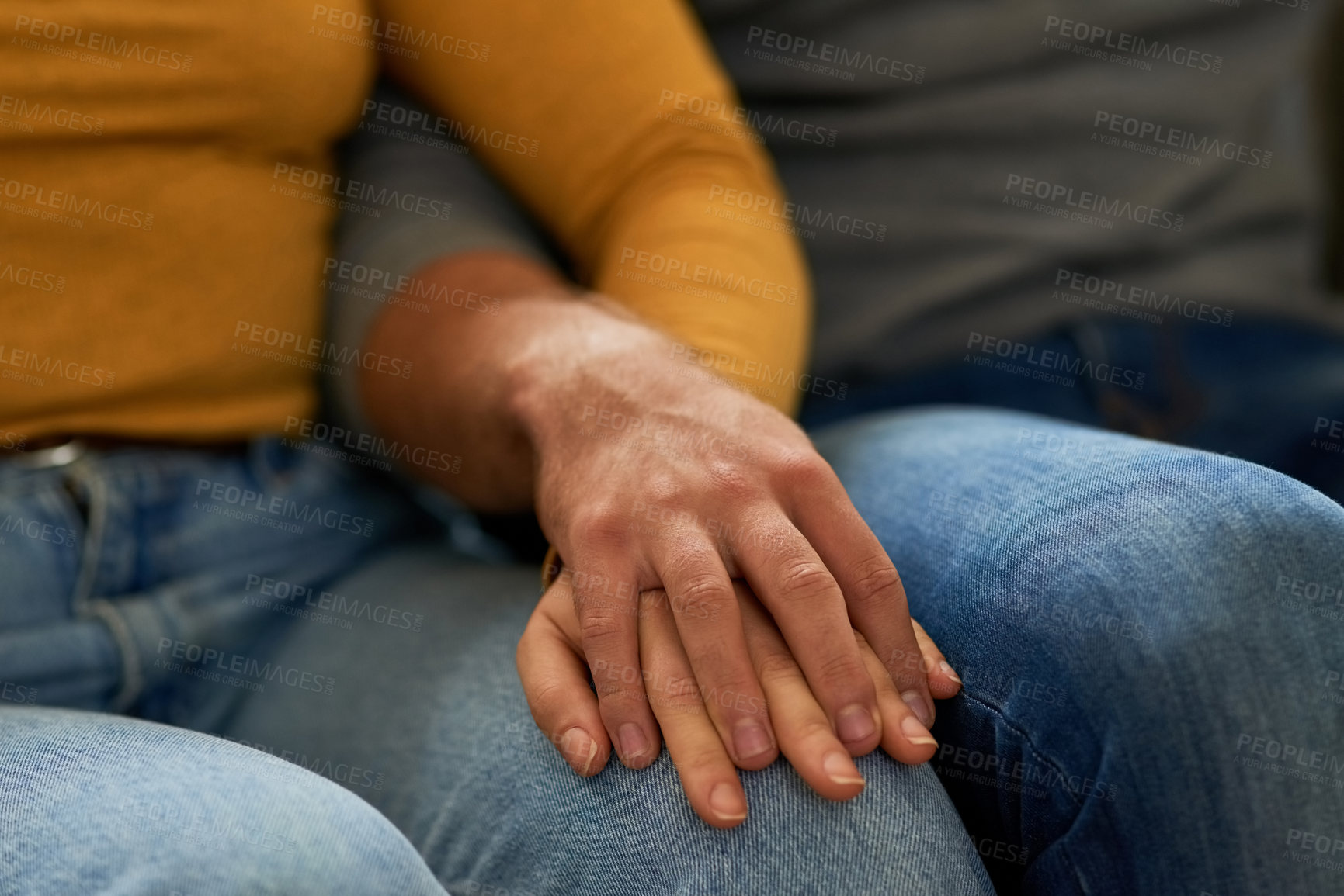 Buy stock photo Closeup shot of an unrecognizable couple holding hands on the sofa in the living room at home