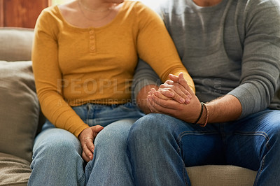Buy stock photo Cropped shot of an unrecognizable couple holding hands on the sofa in the living room at home