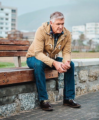 Buy stock photo Full length shot of a senior man looking depressed while sitting on a bench near the beach