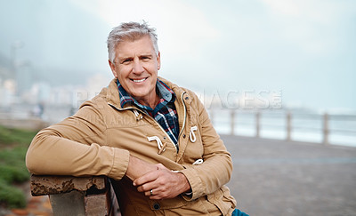Buy stock photo Cropped portrait of a handsome senior man sitting on a bench near the beach