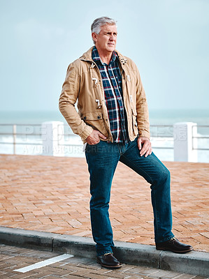 Buy stock photo Full length shot of a handsome senior man standing on the promenade at the beach