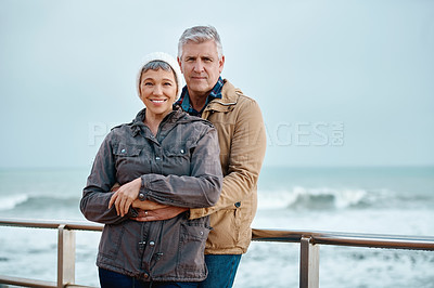 Buy stock photo Cropped portrait of an affectionate senior couple standing on the promenade at the beach